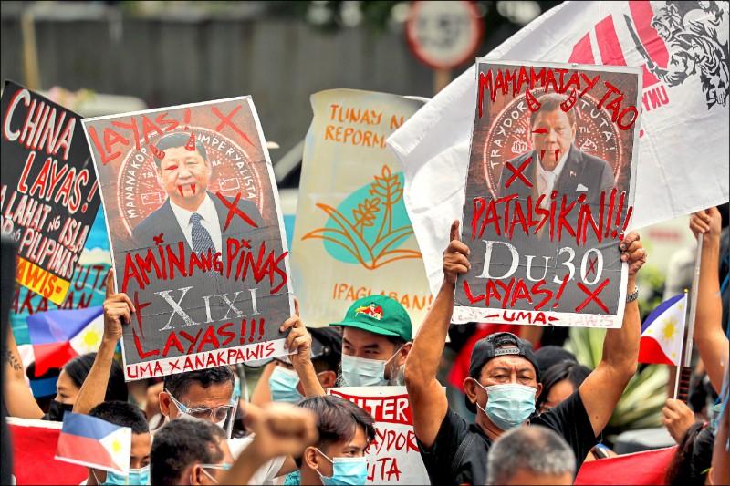 菲律賓示威者6月12日在大馬尼拉地區馬卡蒂市的中國領事館外,高舉自製海報抗議中國國家主席習近平和菲國總統杜特蒂,傷害菲國主權。(歐新社檔案照)