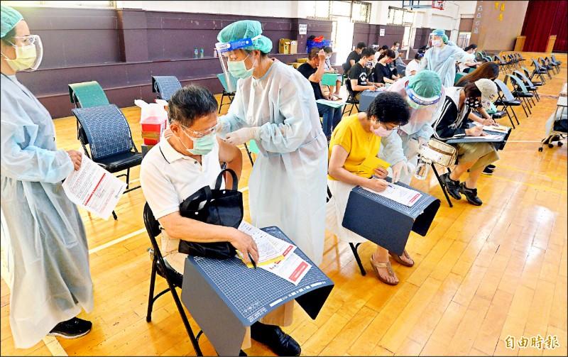 經濟部表示,上月起已逐步針對商業服務業第一線人員進行造冊,包括量販、超商、超市收銀、外送等人員已納入施打對象。圖為北市市場攤商在宏恩醫院施打點打疫苗。 (記者林正堃攝)