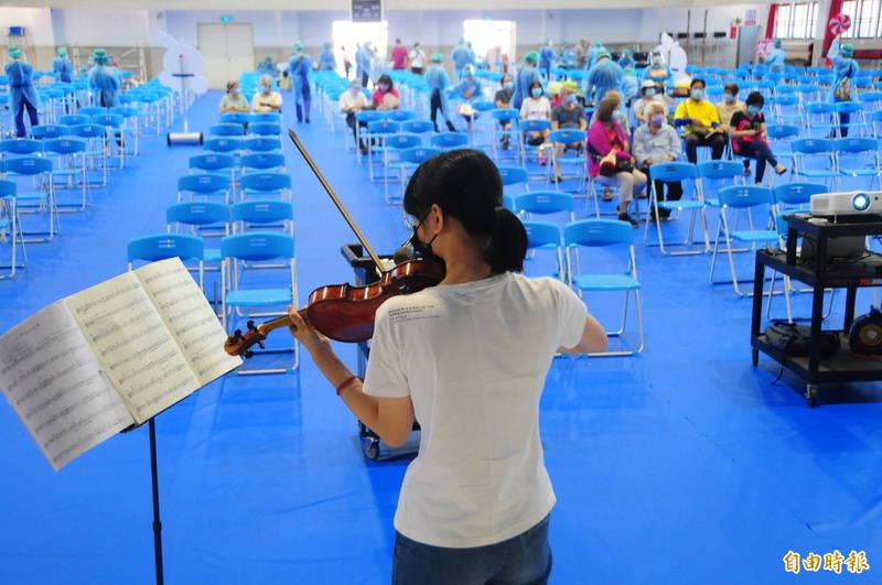 花蓮市花蓮高工接種站今天陸續有1017人前來接種,還能一邊聆聽學生拉小提琴。(記者花孟璟攝)