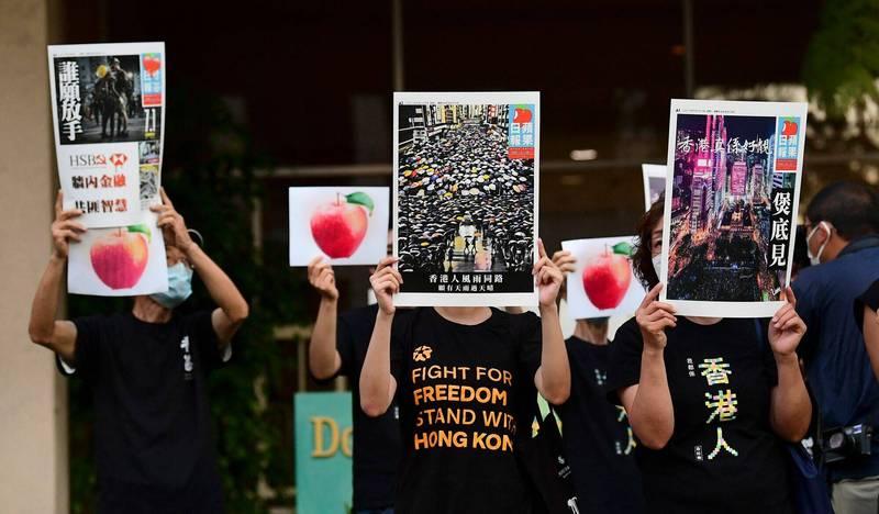 反中共的示威者在7月1日拿著印有香港蘋果日報的傳單,在洛杉磯中國領事館前舉行「中共百年建黨喪禮」抗議行動。(法新社)