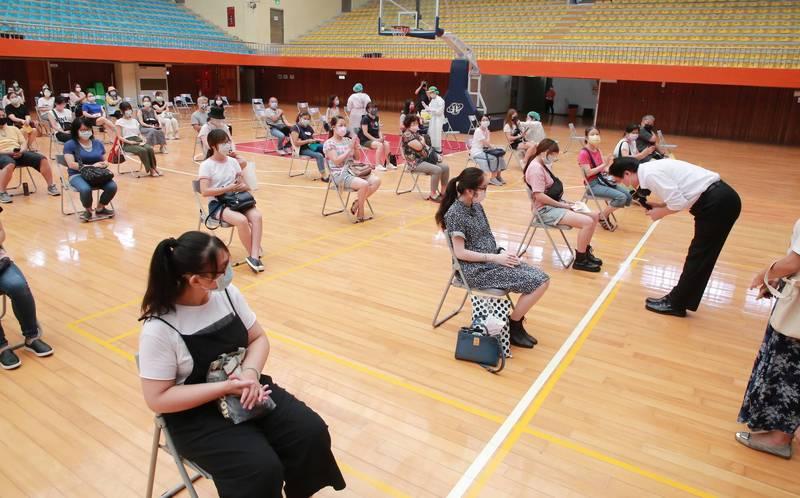 基隆市公私立幼兒園共1045名教職員施打疫苗,市長林右昌(鞠躬者)視察時向他們鞠躬致謝。(基隆市政府提供)