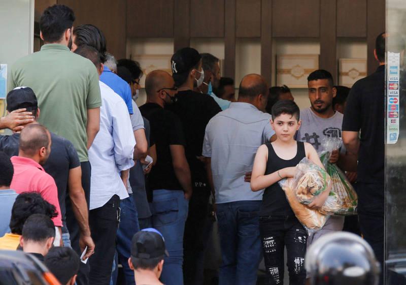 黎巴嫩首都貝魯特民眾排隊等候購買食品。(路透資料照)