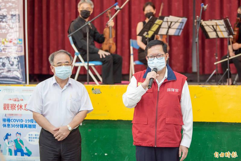 鄭文燦(右)視察平鎮區南勢國小接種站,呼籲市民上網完成接種的意願登記。(記者李容萍攝)