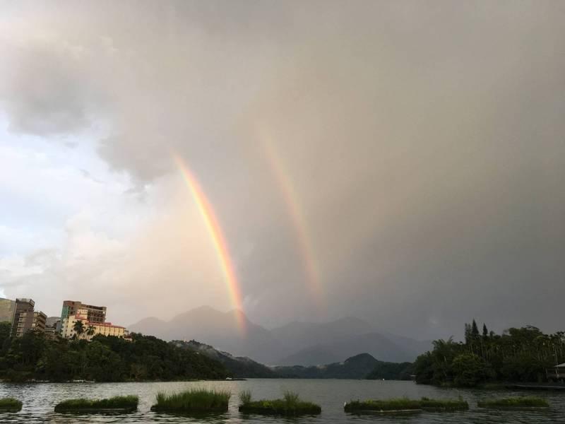 南投日月潭風景區今天傍晚雨後出現少見的雙彩虹;疫情趨緩,國內三級管制也將放寬部分規定,旅遊景點算是盼到雨過天青。(讀者提供)