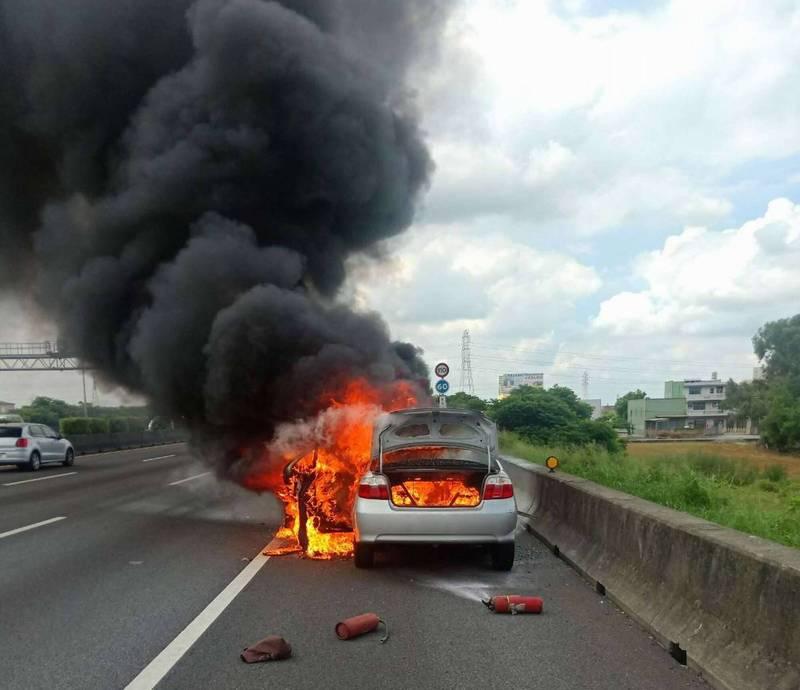1輛轎車行經國1南下199公里時突然冒出濃煙,火勢瞬間吞噬整輛車,駕駛跳車逃命。 (消防局提供)