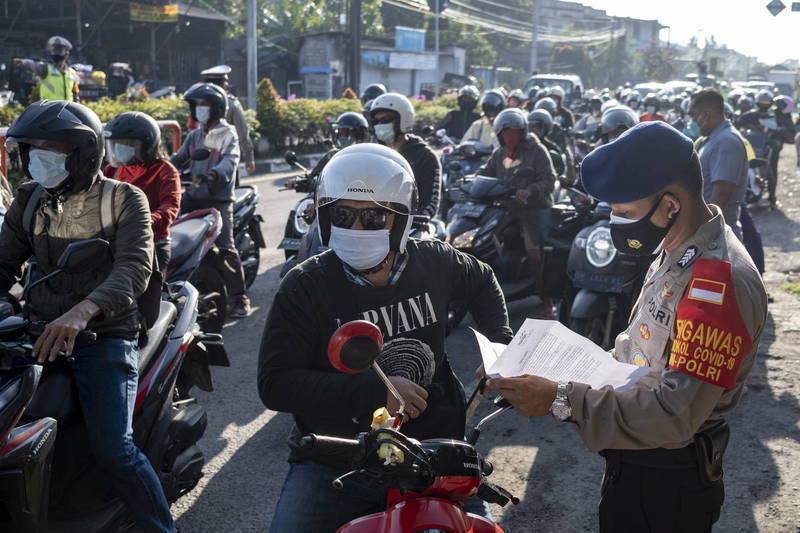 印尼武漢肺炎疫情嚴峻,警察對移動人口檢查管制。(歐新社)
