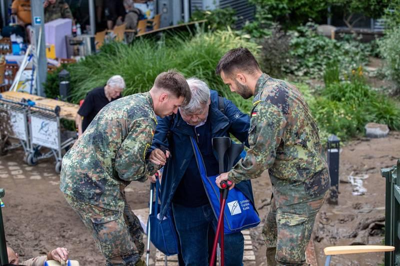 西歐暴雨造成河川潰堤,德國、比利時的死亡人數已攀升至70人,而且還有多人失蹤。圖為德國軍人救助民眾。(歐新社)