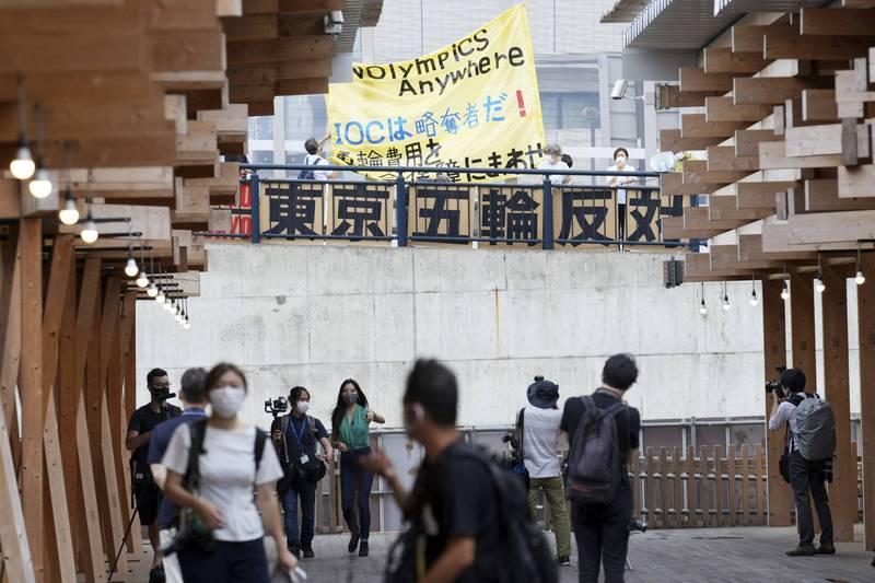 日本東京奧運選手村傳出首起武漢肺炎病例。圖為選手村與抗議奧運舉行的民眾。(美聯社)