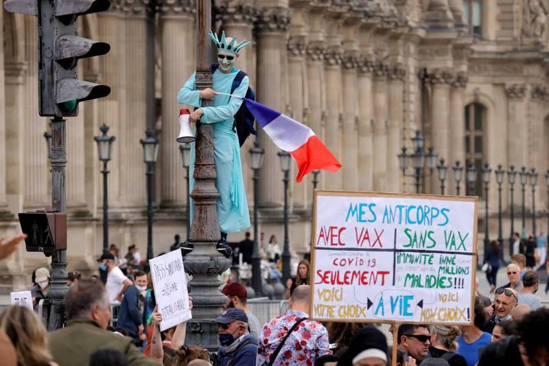 法國總統馬克宏12日宣布將擴大健康通行證使用範圍,不少示威群眾抗議新政策。(路透)