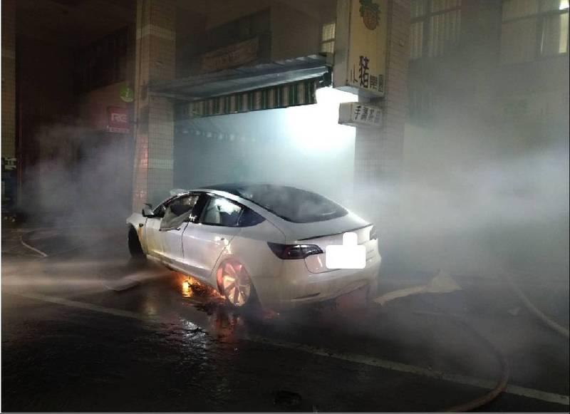 特斯拉電動車自撞民宅水泥柱後底盤起火燃燒。(圖:南市消防局提供)