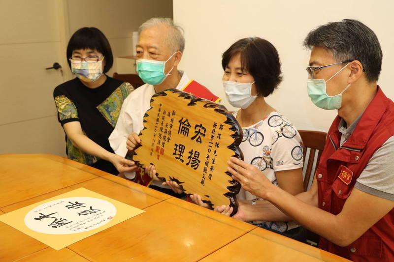 新北市社會局長張錦麗(左)與汐止區長陳健民(右)將模範父親賀匾送至鄭茂林(左二)家中。(圖由社會局提供)