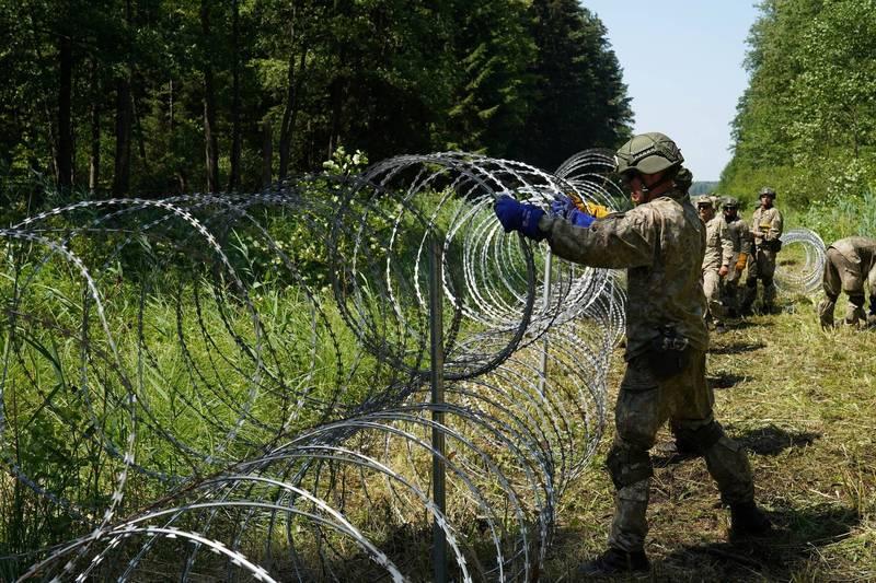 歐盟境管局今(19)日表示,將在下週於白俄羅斯和立陶宛邊境設置約60名的邊境守衛,以管制該邊境的安全。圖為立陶宛士兵正在國界上搭建鐵絲網。(路透)