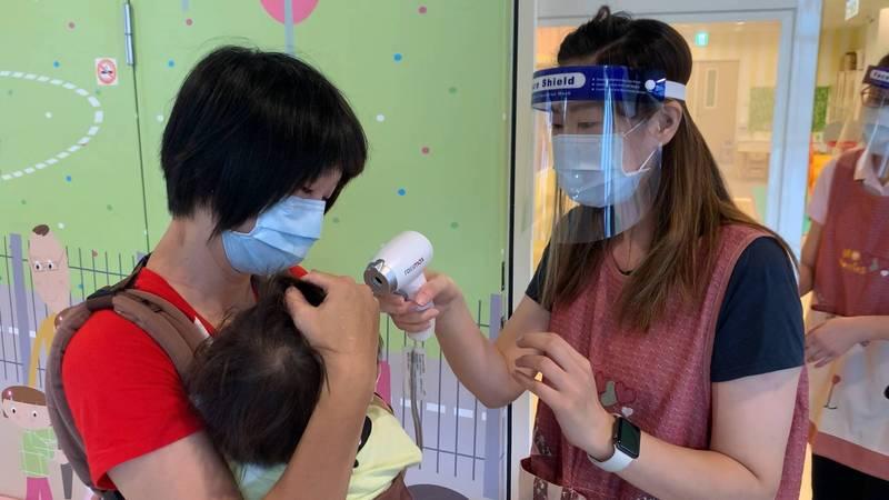 台北市公私立托嬰機構恢復收托,一早就有家長送孩子到機構,機構員工替幼兒量測體溫。(圖由北市社會局提供)