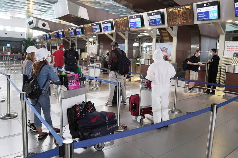 日本虽已安排特别航班协助旅居印尼的日人返国,但机位根本不够,而且价格高得令人咋舌。图为9日旅客在印尼的苏加诺-哈达国际机场的报到柜台前排队等候办理登机手续。(彭博社)(photo:LTN)