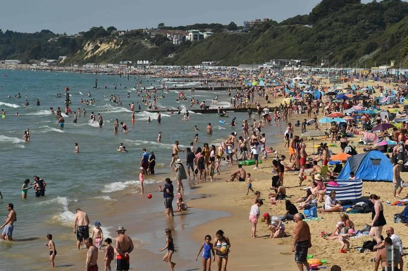 近日天氣炎熱,英國南部多塞特郡的伯恩茅斯海灘聚集許多民眾消暑玩耍。(法新社)
