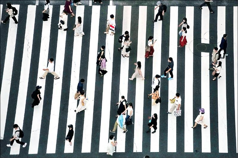 日本東京都政府二十二日宣布武漢肺炎單日新增確診人數來到一九七九人,在東京奧運二十三日開幕前逼近兩千人大關。圖為戴著口罩的民眾二十二日走在東京一條行人穿越道上。(美聯社)
