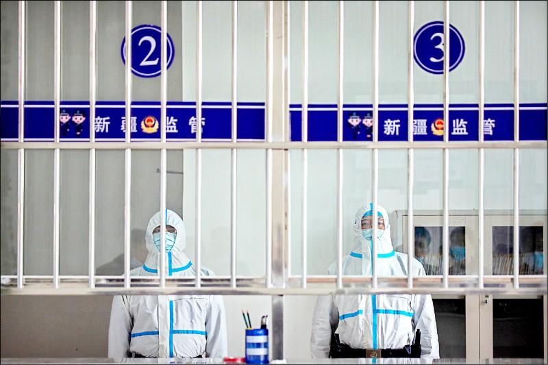 美聯社記者獲准進入烏魯木齊市第三看守所內參訪,看到看守所訪客大廳的接待人員身著全套防護衣。(美聯社)