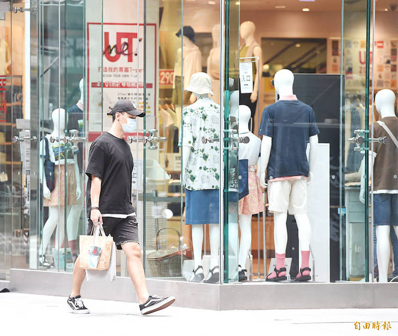 A man walks past a department store window in Taipei's Ximending shopping area yesterday. Photo: Fang Pin-chao, Taipei Times