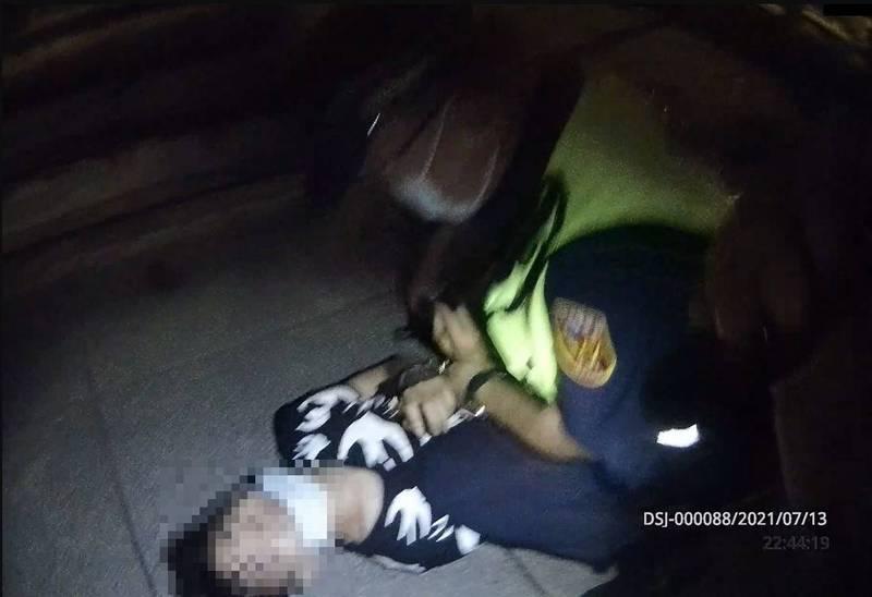潘姓男子在武漢肺炎疫情警戒期間,未戴口罩,蹲坐路旁抽菸,警方發現槍藏腰際後,將他壓制在地。(記者林嘉東翻攝)