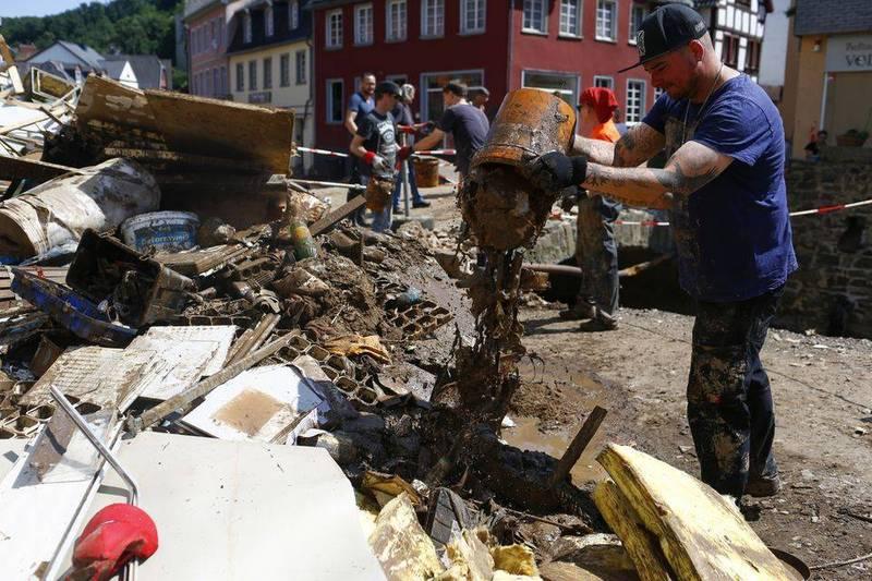 德國受洪災重創,政府將授權行動網路業者傳送緊急簡訊,以便民眾日後因應。圖為德國民眾清理災情後的現場。(路透)
