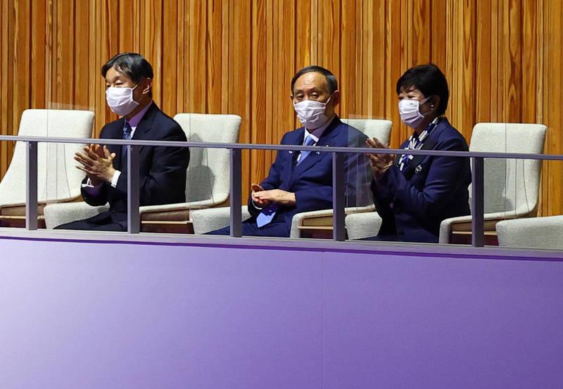 日本東京奧運23日盛大展開,日本德仁天皇(左)出席開幕典禮致詞,他旁邊的首相菅義偉(中)、東京都知事小池百合子(右)被網友發現坐著聽天皇發言,2人後來才倉促站起,畫面曝光被罵爆。(路透)