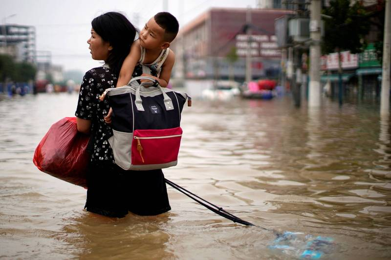 中國河南鄭州市遭逢水災,造成嚴重死傷及災損。圖為23日一名鄭州居民帶著孩子涉水的畫面,示意圖。(路透)
