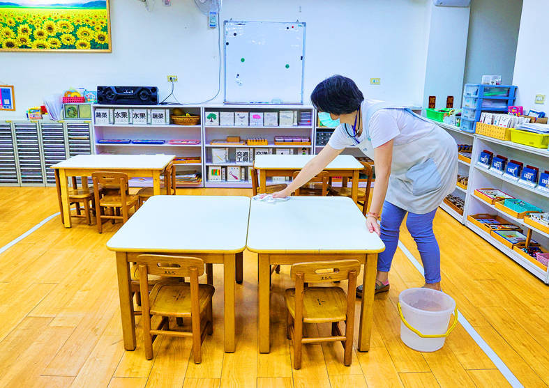 A staff member at a kindergarten in Taipei on Friday wipes tables in preparation for the school's conditional reopening after a nationwide COVID-19 alert is lowered from level 3 to level 2 on Tuesday. Photo: CNA