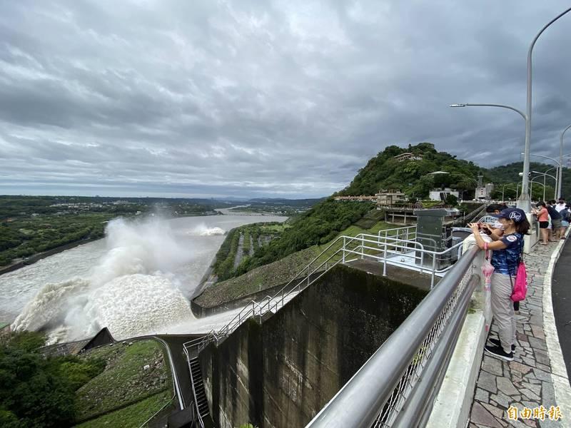 烟花颱風外圍環流降下大雨,桃園石門水庫接近滿水位,今(24日)上午10點開啟溢洪道洩洪。(記者許倬勛攝)