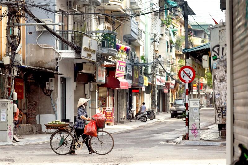 為讓疫情降溫,越南首都河內自廿四日起封城。圖為一名小販行經河內街頭。(歐新社)