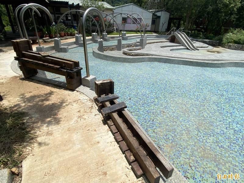 埔里鎮桃米生態村親水公園,目前還有固定式仿木椅等2期工程進行,暫不開放。(記者佟振國攝)
