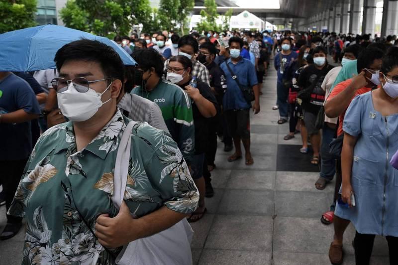 泰國疫情嚴峻,確診人數迭創新高。圖為首都曼谷民眾,在挽賜中央車站,排隊等著接種疫苗。(法新社)