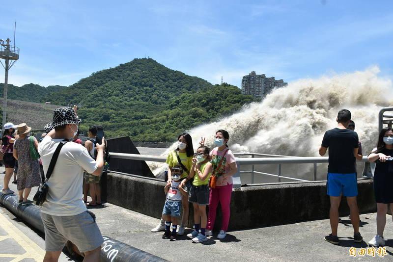 民眾闔家前往石門水庫觀看場面超壯觀的排洪,大家看到水庫有水都很開心。(記者李容萍攝)