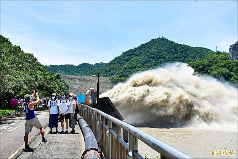 因疫情久未出遊的民眾,觀看石門水庫洩洪壯觀場面超開心,紛紛拍照合影。(記者李容萍攝)