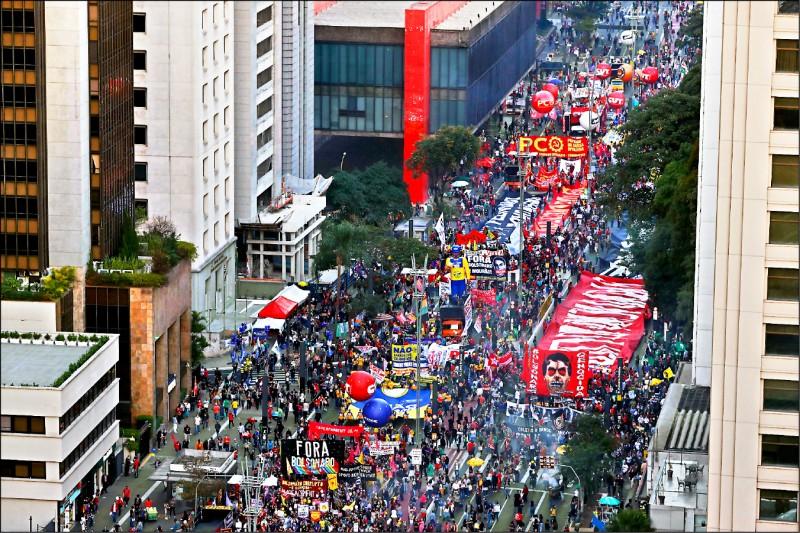 成千上萬的民眾二十四日走上巴西最大城聖保羅街頭,要求彈劾未能妥善處理武漢肺炎疫情的總統波索納洛。(路透)