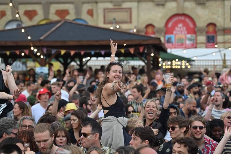 英格蘭徹底解封後,上週感染率驟降42%。圖為群眾不戴口罩,參加倫敦24日的音樂節活動。(法新社)