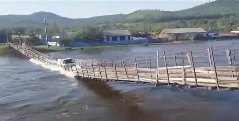 俄羅斯東部烏留姆地區,一輛卡車渡河時橋身斷裂,卡車被淹沒水中。(圖擷取自推特RebeccaRambar)