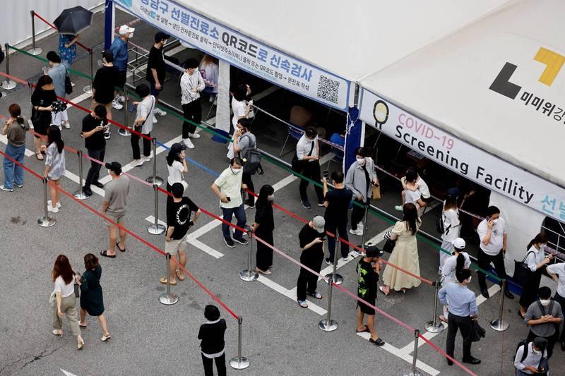 圖為南韓民眾排隊等待接受武肺篩檢。(路透)