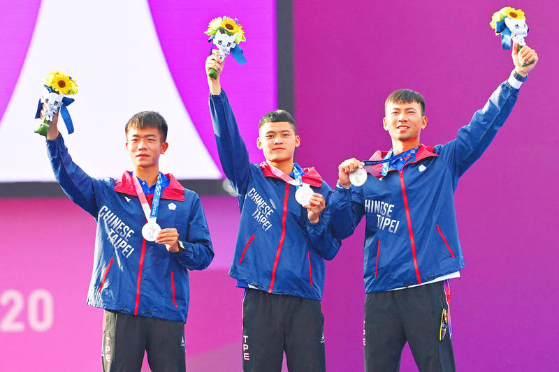 From left, Taiwanese silver medalists Deng Yu-cheng, Tang Chih-chun and Wei Chun-heng celebrate on the podium during the men's team victory ceremony at the Tokyo 2020 Olympic Games at Yumenoshima Park Archery Field in Tokyo yesterday. Photo: AFP