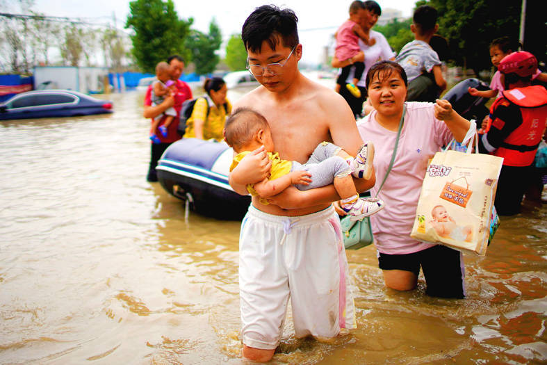 A man holding a baby wades through a flooded road following heavy rainfall in Zhengzhou, Henan Province, China, on Thursday. Photo: Reuters