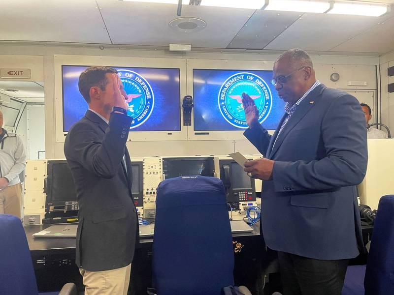 美國國防部長奧斯汀(右)在飛往新加坡的軍機上,為中國工作小組負責人瑞特納(左),就任五角大廈負責印太安全事務的助理國防部長監誓。(路透)