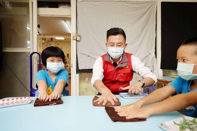幼兒園復課第一天,市長林智堅視察幼兒園防疫,與學童一起消毒桌面。(市府提供)