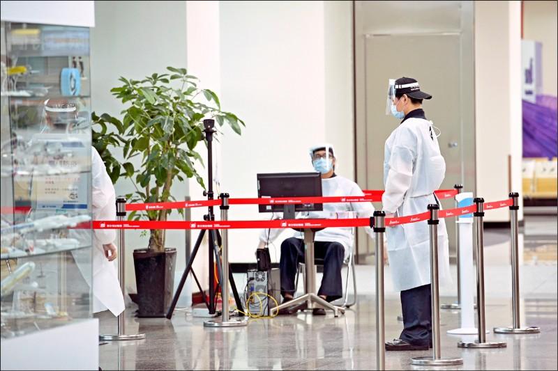 疫情指揮中心指揮官陳時中昨表示,若有就學、工作必要而出國,不見得要在台灣打疫苗,可以到當地再打。圖為松山機場出入口的管制人員穿著防護服執勤。(資料照)