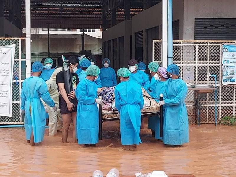 東南部城鎮米瓦迪的醫護人員及志工正試著在淹水的街上把仍須依靠氧氣瓶供氧的病患抬出。(圖擷自克倫資訊中心臉書)