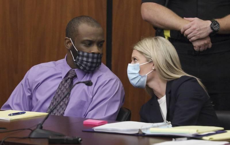 被告納撒尼爾·羅蘭(Nathaniel Rowland)在審判期間與他的律師艾麗西亞·古德(Alicia Goode)交談。(美聯社)