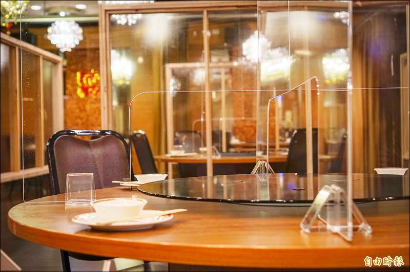 業者將轉盤圓桌,特製下方鏤空的透明隔板,還加上「關節」,既可收納又便利圓桌使用。(記者陳彥廷攝)