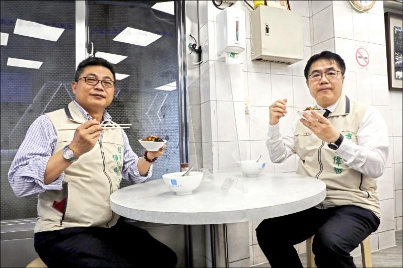 台南市長黃偉哲(右)、經發局長陳凱凌(左)昨天視察永記魚丸湯,示範餐桌要用透明隔罩。(南市經發局提供)