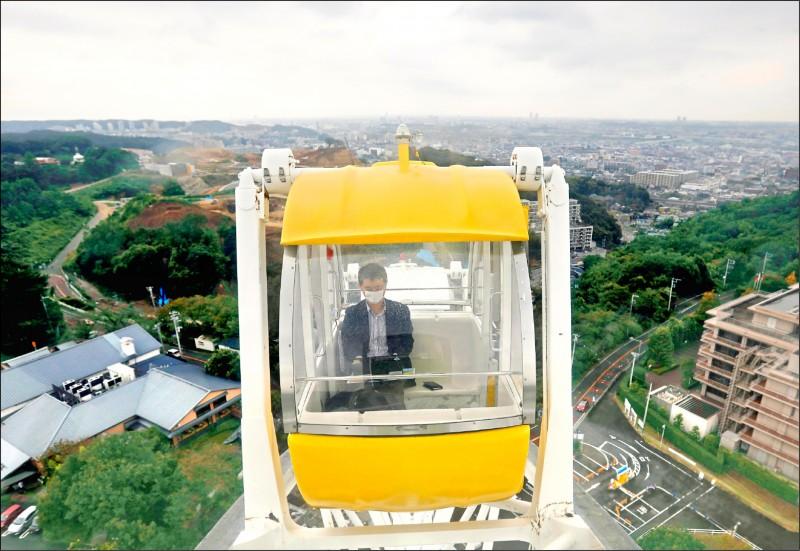 日本讀賣樂園去年推出「遊樂園渡假工作」,一名遠距工作者搭摩天輪時邊處理公事。(路透)