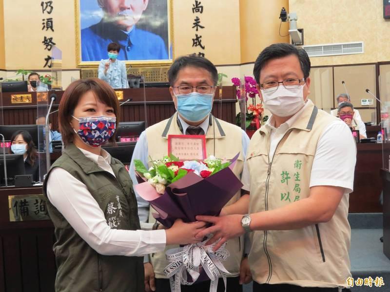 南市議員蔡筱薇(左)在市長黃偉哲(中)見證下,獻花給衛生局長許以霖(右),表達對他及防疫人員的肯定及感謝。(記者蔡文居攝)