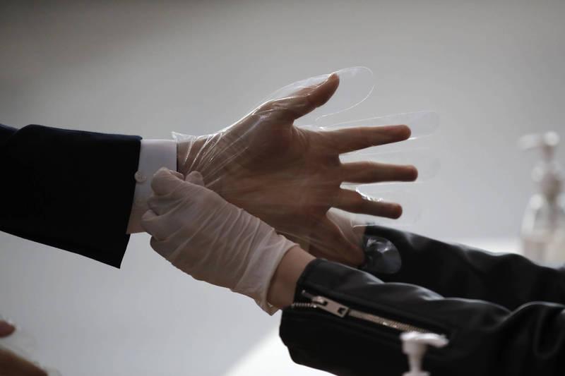 胸腔暨重症專科醫師黃軒表示,研究指出「一個人戴上手套,因感到安全而觸摸電梯等按鈕,反而可能導致病毒更易傳播,且手套不會阻隔病毒又容易穿破」,強調「勤洗手才是不二法門」。戴手套示意圖。(美聯社)