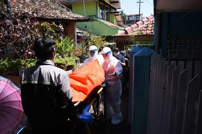 全球累計至少417萬9675人死於武漢肺炎,至少1億9524萬4860例確診,印尼疫情嚴重,27日單日死亡人數達到2069人,圖為印尼萬隆市防疫人員協助處理染疫者遺體的畫面。(法新社)